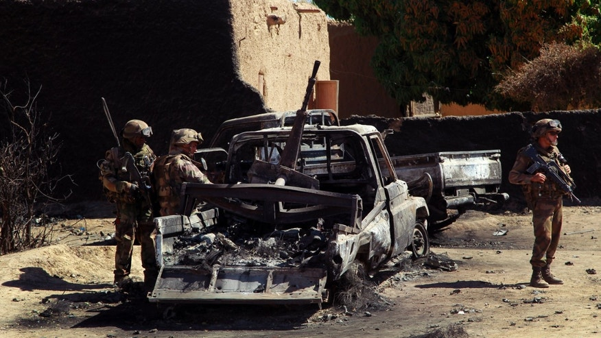 Jan. 21, 2013: In this file photo, French troops inspect the charred remains of  trucks used by radical Islamists, on the outskirts of Diabaly, Mali.