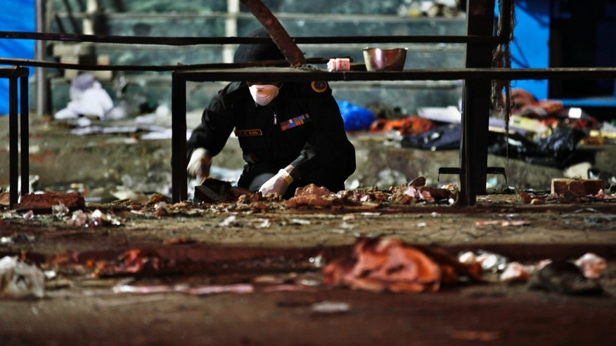 An official of India's National Investigation Agency collects evidence from the debris at one of the two bomb blast sites, in Hyderabad, India, early Friday, Feb. 22, 2013. A pair of bombs exploded Thursday evening in a crowded shopping area in the southern Indian city of Hyderabad, killing at least 12 people and wounding scores of others in the worst bombing in the country in more than a year, officials said. (AP Photo/Aijaz Rahi)