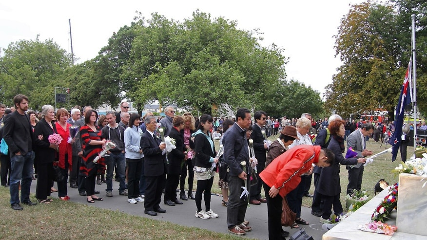 People pay their respects during a memorial service on the second anniversary of a deadly earthquake in Christchurch, New Zealand, Friday, Feb. 22, 2013. Several hundred people gathered for a memorial service in Latimer Square, near where 115 died when a six-story office building collapsed during the magnitude-6.1 quake. (AP Photo/New Zealand Herald, Geoff Sloan) NEW ZEALAND OUT, AUSTRALIA OUT