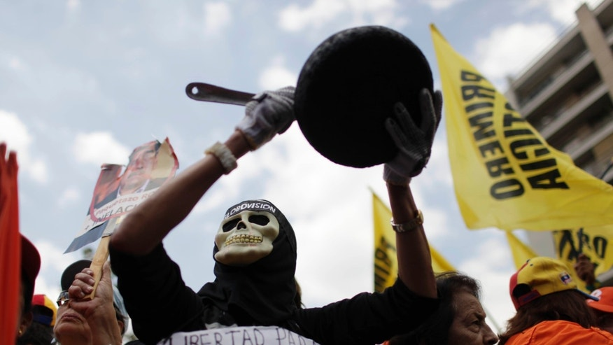 A protester dressed as a death holds up pan during an opposition demonstration against of the devaluation of the currency in Caracas, Venezuela, Saturday, Feb. 23, 2013. Venezuela's government announced on Friday, Feb. 8 that it is devaluing the country's currency, a long-anticipated change expected to push up prices in the heavily import-reliant economy. Venezuela's government has had strict currency exchange controls since 2003 and maintains a fixed, government-set exchange rate. While those controls have restricted the amounts of dollars available at the official rate, an illegal black market has flourished and the value of the bolivar has recently been eroding.  (AP Photo/Ariana Cubillos)
