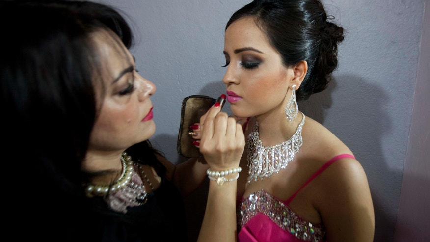 "ADVANCE FOR USE SUNDAY, FEB. 24, 2013 AND THEREAFTER - In this Jan. 26, 2013 photo, Magdabelyn Parra Gamez, who goes by Belyn, holds still as her lipstick is applied backstage as she competes in the ""Guamuchil Carnival Queen 2013"" beauty pageant in Guamuchil, Sinaloa state, Mexico.  Belyn, 18, took up the mantle on the pageant circuit after the death of her cousin beauty queen Maria Susana Flores Gamez, who in November 2012 died like a mobster's moll, carrying an AK-47 assault rifle into a spray of gunfire from Mexican soldiers. ""This is in memory of Susy,"" Belyn whispered, shortly before winning the crown, ""In honor of her."" (AP Photo/Eduardo Verdugo)"