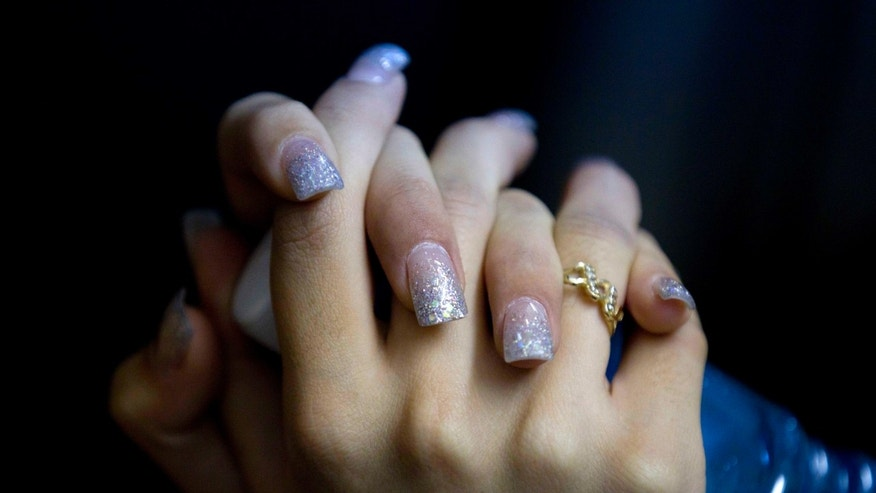 "ADVANCE FOR USE SUNDAY, FEB. 24, 2013 AND THEREAFTER -  This Jan. 26, 2013 photo shows a detail of a beauty contestant's nails during the ""Guamuchil Carnival Queen 2013"" beauty contest in Guamuchil, Sinaloa state, Mexico. The farming town of 60,000 in the state of Sinaloa, despite its unpaved roads, is full of big mansions hidden behind high walls and iron doors decorated with ornate mirrors and life-size statues of angels. The town has produced at least a Miss Mexico and more recently prides itself in saying the runner up to Miss World 2009 is a native.(AP Photo/Eduardo Verdugo)"