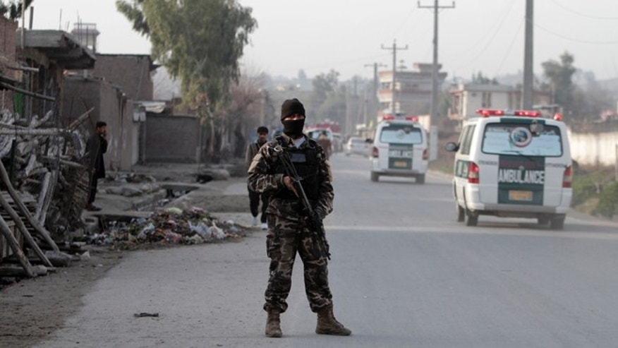 Feb 24, 2013: A security official stands guard the scene of a suicide car bomb attack which killed and injured several people at the National Directorate of Security in Jalalabad, Afghanistan.