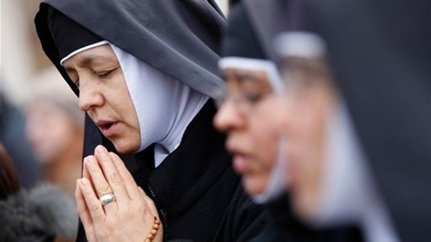 Feb. 24, 2013: Nuns pray prior to Pope Benedict XVI's last Angelus noon prayer, in St. Peter's Square, at the Vatican.