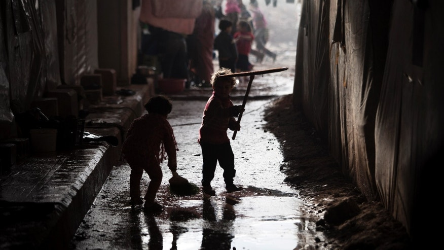 Displaced Syrian children play with cleaning tools in the Azaz camp for displaced people, north of Aleppo province, Syria, Thursday, Feb. 21, 2013. According to Syrian activists the number of people in the Azaz camp has grown by 3,000 in the last weeks due to heavier shelling by government forces. (AP Photo/Manu Brabo)