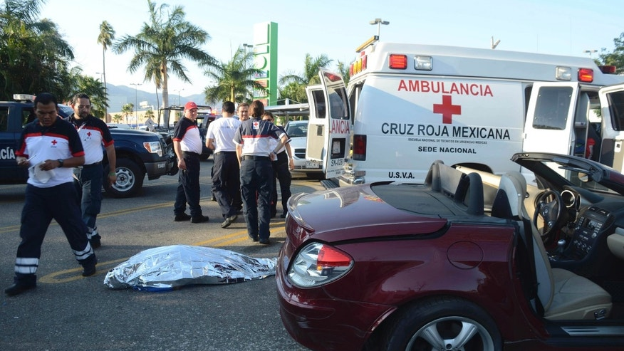 Emergency responders stand next to the body of a man identified as a Belgian citizen as he lies in the ground next to his car after he was shot dead by unknown assailants while he was leaving a supermarket in the Pacific resort city of Acapulco, Mexico, Saturday Feb. 23, 2013. The incident occurred a very short distance away from the Fairmont Acapulco Princess where the Mexico Tennis Open is slated to begin next Monday. (AP Photo/Bernandino Hernandez)