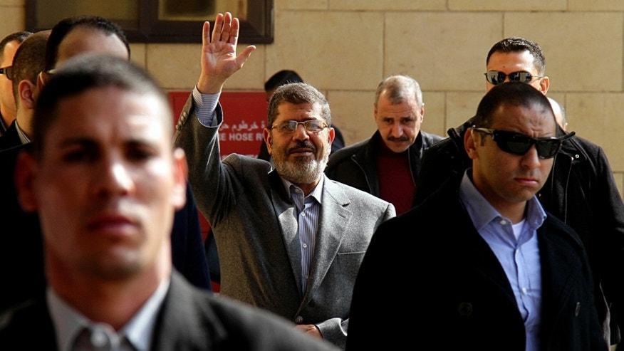 "In this Friday, Jan. 4, 2013 file photo, Egyptian President Mohammed Morsi, center, waves to supporters after attending Friday prayers at the Hassan Sharbatli mosque on the outskirts of Cairo, Egypt. Morsi, in a rambling 2.15-hour TV interview that aired in the early hours of Feb, 25, 2013, dismissed the masses protesting against his rule across much of the nation as ""thugs"" and ""outlaws."""