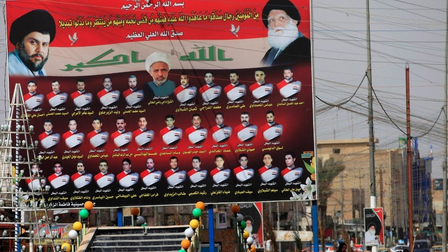 Feb. 24, 2013 - Iraqi women walk past a billboard showing Shiite religious leaders and Shiites who were killed during a fight between US troops and al-Mahdi Army militia in the Jihad neighborhood of west Baghdad, Iraq.