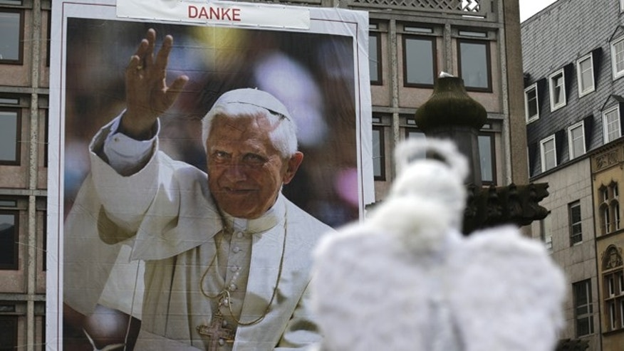 An artist dressed as an angel poses for tourists in front of a huge Pope Benedict XVI poster in Cologne, Germany, on Tuesday, Feb.26,2013. The words on top read:'Thanks'.  Pope Benedict XVI will resign on February 28th. The poster is used as advertisement for radio channel 'domradio'. .(AP Photo/Frank Augstein)