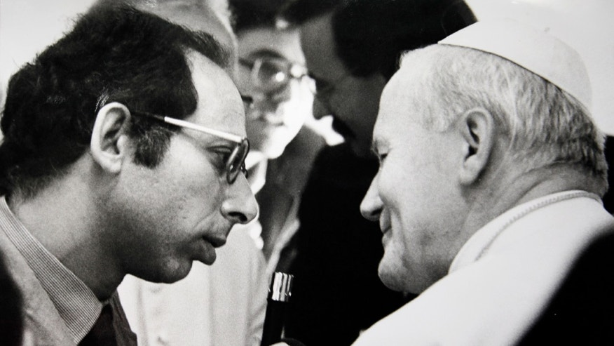 This June 2, 1979 photo shows then Associated Press correspondent Victor Simpson, left, interviewing Pope John Paul II aboard the airplane in flight from Rome to Warsaw, June 2, 1979. Rome Bureau Chief Victor Simpson has chronicled four papacies in 35 years covering the Holy See. A Vatican institution in his own right, Simpson has had a unique vantage point on history, enjoying the ear of Vatican insiders and chatting with the pope himself on foreign pilgrimages.  (AP Photo)