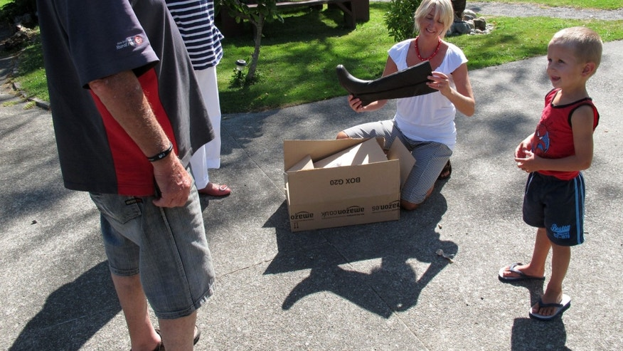 In this photo taken Friday, Feb. 15, 2013, Sandra Vidulich is thrilled about her new leather boots delivered by postman John Lahmert in rural Otaki, New Zealand.  New Zealand is considering cutting letter deliveries from six days a week to three as global demand for postal services dwindles.  (AP Photo/Nick Perry)