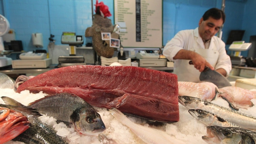 FILE -- In this June 12, 2012 file photo, a piece of yellowfin tuna, top, is displayed at a fish shop in Ghent, Belgium. On Wednesday, Feb. 27, 2013 Officials from the 27 European Union countries approved a proposal on a phased ban on vessels discarding of unwanted fish, but environmentalists are condemning the measure as too weak. The aim is to preserve fish stocks, some of which are dwindling dangerously. (AP Photo/Yves Logghe, File)