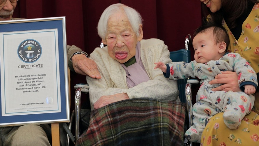 Japan's 114-year-old Misao Okawa, center,  poses with her 2-month-old great-grandson Hibiki Okawa  along with the Guinness World Records certificate at a nursing home in Osaka, western Japan, Wednesday, Feb. 27, 2013.  Okawa has been recognized as the world's oldest woman by Guinness World Records on Wednesday. (AP Photo/Itsuo Inouye)