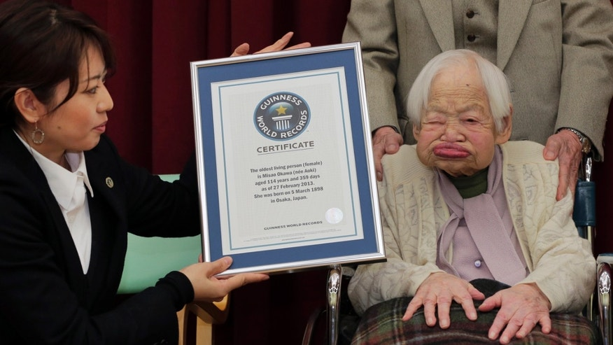 Japan's 114-year-old Misao Okawa, right, poses with the certificate of the world's oldest living woman, which was presented to her by Guinness World Records Japan Country Manager Erika Ogawa, right,  at a nursing home in Osaka, western Japan, Wednesday, Feb. 27, 2013.  (AP Photo/Itsuo Inouye)