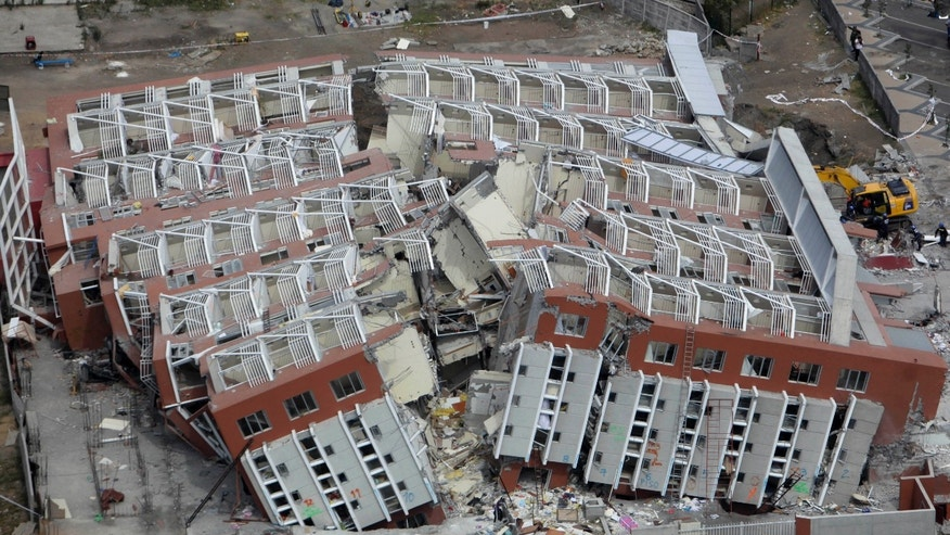 FILE - In this March 4, 2010 file photo, a collapsed building lays in ruins after an earthquake in Concepcion, Chile.  Wednesday, Feb. 27, 2013 marks the three year anniversary of the 8.8-magnitude earthquake that struck central Chile that killed over 500 people, destroyed over 200,000 homes and washed away docks and seaside resorts, costing Chile $30 billion, or 18 percent of its annual gross domestic product. (AP Photo/Natacha Pisarenko, File)