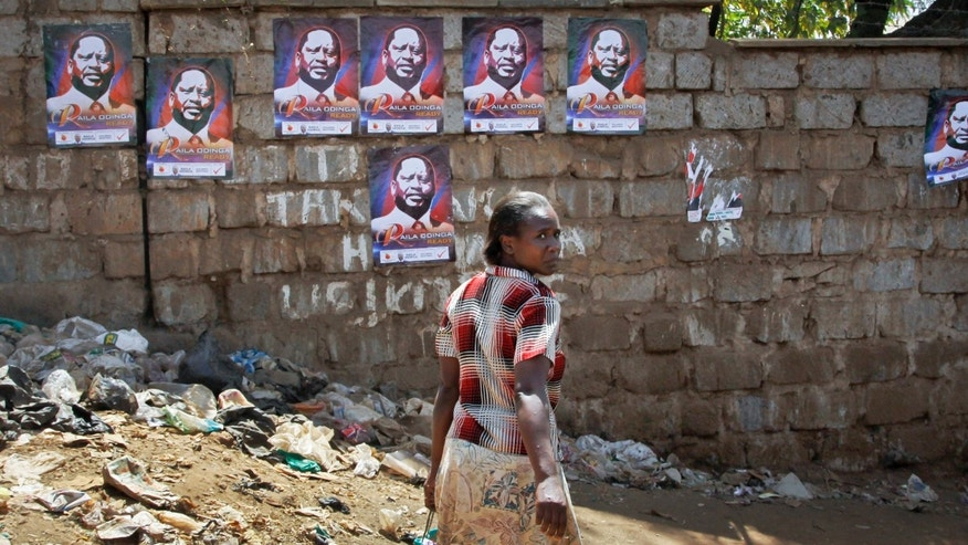 In this photo taken Monday, Feb. 25, 2013, a woman walks past election campaign posters of presidential aspirant Raila Odinga in the Kibera slum of Nairobi, Kenya. Kenya on Monday holds its first presidential election since its 2007 vote devolved into months of tribal violence, and in recent weeks in Nairobi's most dangerous slum Mathare dozens of tin shack homes have been burned to the ground and some families are moving into zones controlled by their own clans. (AP Photo/Khalil Senosi)