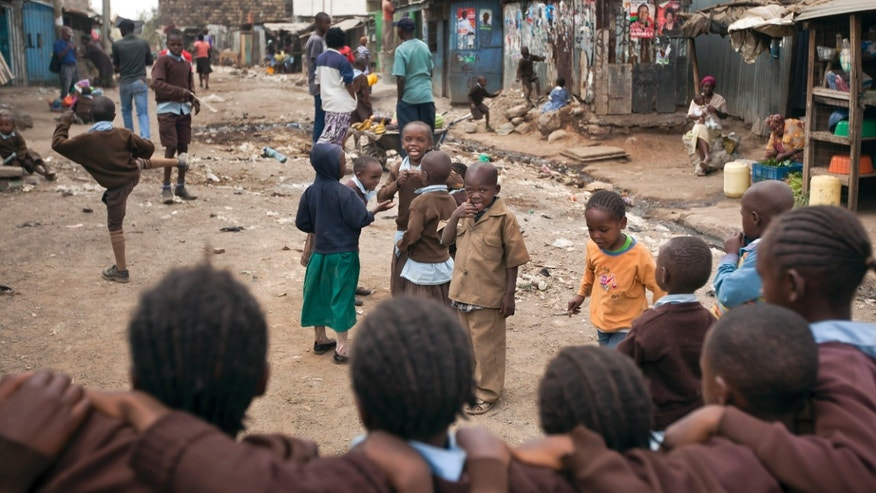 In this photo taken Tuesday, Feb. 26, 2013, children play street games in an alley of the Mathare slum of Nairobi, Kenya. Kenya on Monday holds its first presidential election since its 2007 vote devolved into months of tribal violence, and in recent weeks in Nairobi's most dangerous slum Mathare dozens of tin shack homes have been burned to the ground and some families are moving into zones controlled by their own clans. (AP Photo/Ben Curtis)