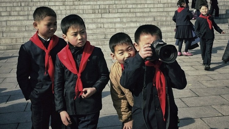 Feb. 16, 2013: In this photo taken with an iPhone and posted to Instagram, North Korean school boys play with an Associated Press photographer's professional camera in front of statues of the late leaders Kim Il Sung and Kim Jong Il, on Mansu Hill in Pyongyang, North Korea.