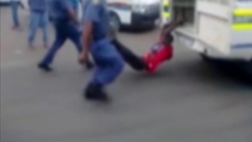 Feb 26, 2013 - This TV image shows a man with his hands tied to the back of a police vehicle east of Johannesburg.