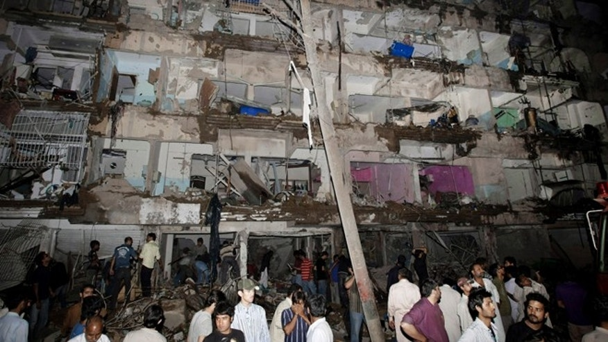 March 3, 2013: Pakistanis gather at the site of a bomb blast in Karachi, Pakistan. Pakistani officials say a bomb blast has killed dozens of people in a neighborhood dominated by Shiite Muslims in the southern city of Karachi.