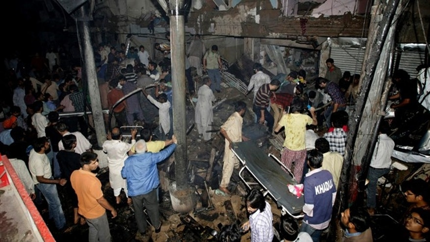 March 3, 2013: Pakistani medics and civilians gather at the site of a bomb blast in Karachi, Pakistan. Pakistani officials say a bomb blast has killed dozens of people in a neighborhood dominated by Shiite Muslims in the southern city of Karachi.