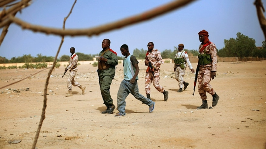 Feb. 6, 2013: Malian soldiers follow a resident to a house formally occupied by Mujao radicals when they fled Gao, northern Mali. Troops from France and Chad moved into Kidal in an effort to secure the strategic north Malian city, a French official said Tuesday, as the international force put further pressure on the Islamic extremists to push them out of their last major bastion of control in the north. (AP)