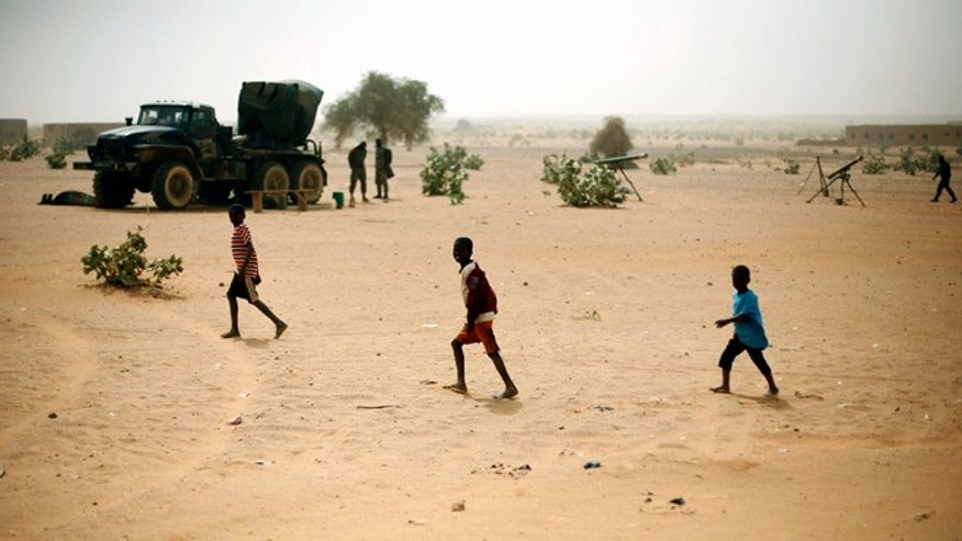 Jan. 31, 2013: Children run in front of Malian artillery positions set near the bridge crossing the river Niger at the entrance of Gao, northern Mali. Islamist extremists fled the city Saturday after French, Chadian and Nigerien troops arrived, ending 10 month of radical Islamic control over the city. (AP)