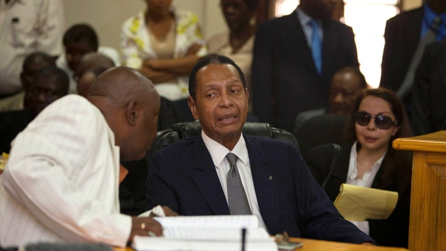 "Feb. 28, 2013: Former Haitian dictator Jean-Claude Duvalier, known as ""Baby Doc,"" center, attends his hearing as his companion Veronique Roy sits behind, right, inside a courthouse in Port-au-Prince, Haiti."