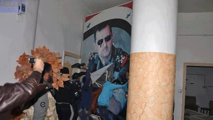 March. 4, 2013 - Citizen journalism image from inside Air Force Intelligence headquarters in Raqqa, Syria shows people tearing down a huge poster of President Bashar Assad and hitting it with their shoes. (provided by Coordination Committee in Kafr Susa)