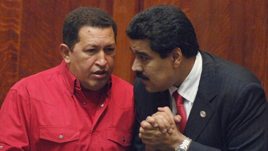 FILE: President Hugo Chavez, left, talks to then Foreign Minister Nicolas Maduro at the University of Uruguay in Montevideo, Uruguay.