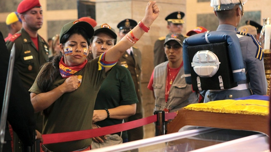 March 7, 2013: In this photo released by Miraflores Press Office, a woman pays her respects, placing a hand on her heart and saluting,  before she files past the glass-topped casket containing the remains of Venezuela's late President Hugo Chavez at the military academy, where he started his army career, in Caracas.