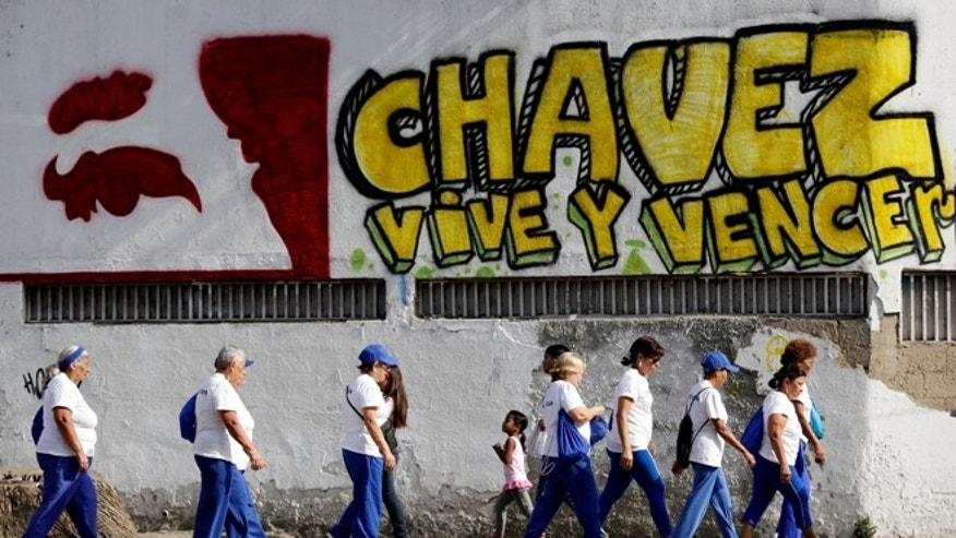 "Pedestrians walks past graffiti that reads in Spanish; ""Chavez lives and will prevail,"" outside the military hospital in Caracas, Venezuela, Tuesday, March 5, 2013. A brief statement read on national television by Communications Minister Ernesto Villegas late Monday carried the sobering news about the charismatic 58-year-old leader's deteriorating health. Villegas said President Hugo Chavez is suffering from ""a new, severe infection."" The state news agency identified it as respiratory. (AP Photo/Ariana Cubillos)"