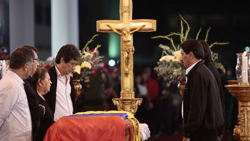 In this photo released by Miraflores Press Office,  Hugo Chavez' mother Elena Frias, third from left, and brothers Adan, second from left, Argenis, first right, and Adelis, fourth from right, stand next to the flag-draped coffin containing the body of Venezuela's late President Hugo Chavez on display during his wake at a military academy where his body will lie in state until his funeral in in state in Caracas, Venezuela, Wednesday, March 6, 2013.