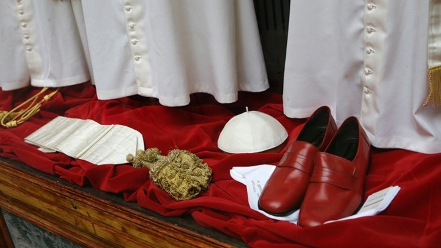"FILE -  In this March 4, 2013 file photo, papal shoes and a white skull cap are seen beneath three sets of papal outfits - small, medium and large sizes - are displayed in the Gammarelli tailor shop window, in Rome. The favorite guessing game in Rome these days is who will be the next pope.  No one takes this more seriously than the Gammarelli family, ecclesiastical tailors by papal appointment for over 200 years. For the past seven conclaves Gammarelli has prepared three identical white outfits in small, medium and large for the new pope when he makes his first public appearance on the balcony of St.Peter's and gives his first blessing to the crowd below. The outfits have been on display in the window of the small wood paneled store nestled in the shadow of the Pantheon, where the family moved in 1850 from the original ""bottega'' (artisan shop) just around the corner founded in 1798. Before the start of the conclave, the outfits will be delivered to the Vatican, and left in a room adjacent to the Sistine Chapel, where the just elected pope will change into his new clothes. (AP Photo/Andrew Medichini, Files)"