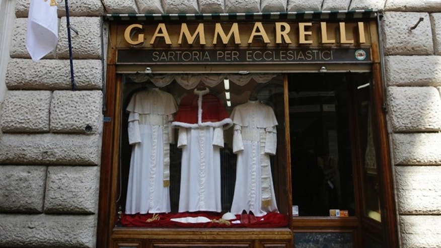 "In this photo taken on March 4, 2013, three sets of papal outfits - small, medium and large sizes - are displayed in the window of the tailoring shop Gammarelli, in Rome. The favorite guessing game in Rome these days is who will be the next pope.  No one takes this more seriously than the Gammarelli family, ecclesiastical tailors by papal appointment for over 200 years. For the past seven conclaves Gammarelli has prepared three identical white outfits in small, medium and large for the new pope when he makes his first public appearance on the balcony of St.Peter's and gives his first blessing to the crowd below. The outfits have been on display in the window of the small wood paneled store nestled in the shadow of the Pantheon, where the family moved in 1850 from the original ""bottega'' (artisan shop) just around the corner founded in 1798. Before the start of the conclave, the outfits will be delivered to the Vatican, and left in a room adjacent to the Sistine Chapel, where the just elected pope will change into his new clothes. (AP Photo/Andrew Medichini)"