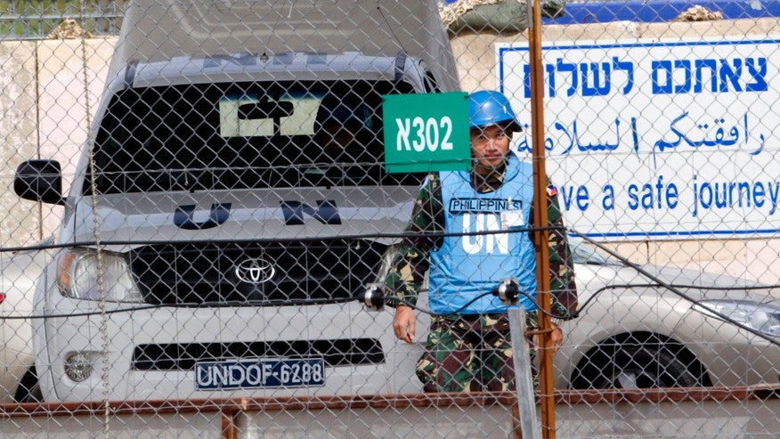 March 7, 2013 - A U.N. peacekeeper from the Philippines crosses back from Syria at the Quneitra Crossing between Syria and the Israeli-controlled Golan Heights.