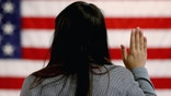 NEWARK, NJ - JANUARY 28:  An woman takes the oath of allegiance during a naturalization ceremony at the at district office of the U.S. Citizenship and Immigration Services (USCIS) on January 28, 2013 in Newark, New Jersey. Some 38,000 immigrants became U.S. citizens at the Newark office alone in 2012.  (Photo by John Moore/Getty Images)