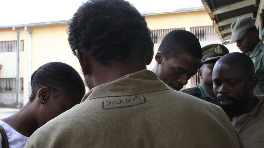 "February, 22, 2013 - George Renene Longange, 41,  shows the back of his prison clothing with the words, ""Super Devil"" inscribed, as he talks to the media at Harare Remand Prison, in Harare, Zimbabwe."