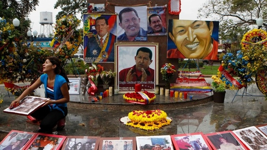 A woman wipes photos of late President Hugo Chavez at a makeshift altar set in his honor at the main square of Sabaneta, western Venezuela on Saturday, March 9, 2013. Chavez, who died of cancer on March 5, 2013 was born in Sabaneta. His former home has been turned into the local headquarters of the United Socialist Party of Venezuela, PSUV. (AP Photo/Esteban Felix)
