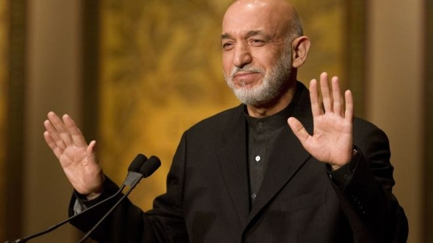 Jan. 11, 2013: Afghanistan President Hamid Karzai gestures for applause to stop before he began his speech at Georgetown University in Washington.
