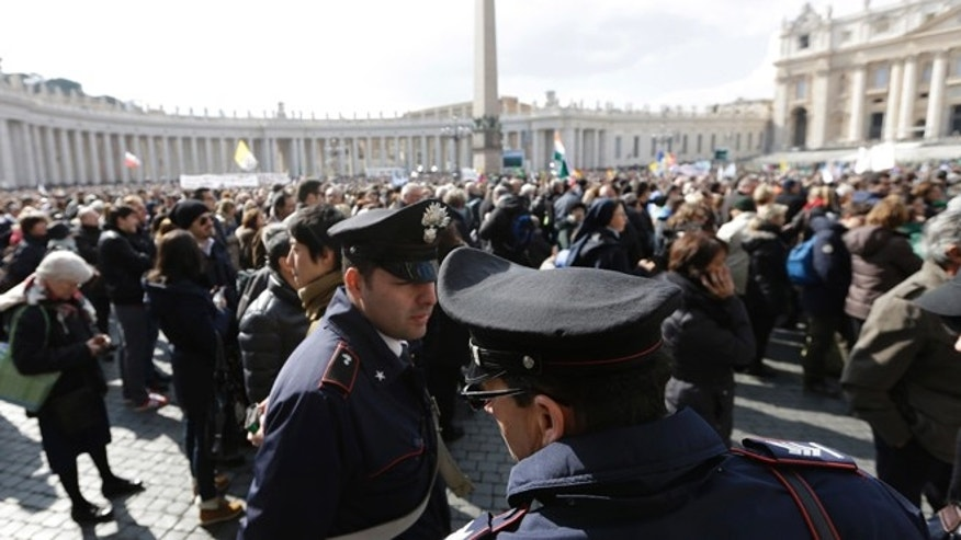 In this file photo taken on Feb. 24, 2013, policeman patrol as faithful gather the last Angelus noon prayer of Pope Benedict XVI, celebrated from the window of his studio overlooking St. Peter.s square at the Vatican. Planning for the moment when the next pope is proclaimed to the world, and for the installation ceremony a few days later, is a big-time guessing game. And that adds up to an ungodly logistical headache for the city of Rome.