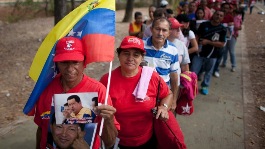 March 10, 2013: People queue outside the military academy where Venezuela's late President Hugo Chavez is lying in state in Caracas, Venezuela. Chavez died on March 5 after a nearly two-year bout with cancer. He was 58.