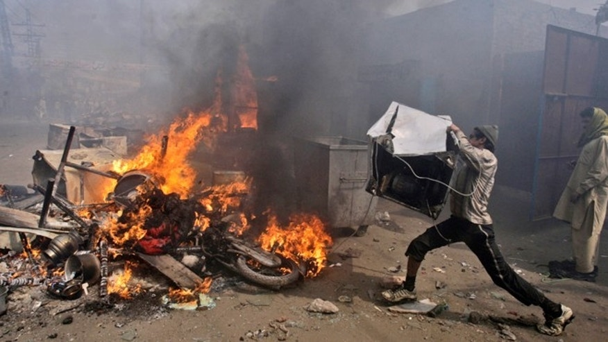 March 9, 2013: A Pakistani man, part of an angry mob, throws items taken from Christian houses into a fire in Lahore, Pakista. A mob of hundreds of people in the eastern Pakistani city of Lahore attacked a Christian neighborhood Saturday and set fire to homes after hearing accusations that a Christian man had committed blasphemy against Islam's prophet, said a police officer.