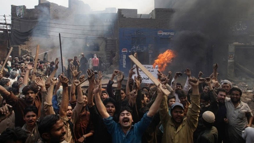 "March 9, 2013: An angry mob reacts after burning Christian houses in Lahore, Pakistan. A mob of hundreds of people in the eastern Pakistani city of Lahore attacked a Christian neighborhood Saturday and set fire to homes after hearing accusations that a Christian man had committed blasphemy against Islam's prophet Mohammed, said a police officer. Placard center reads, ""Blasphemer is liable to death."""