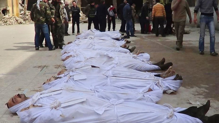 March. 10, 2013 - Syrians standing next to dead bodies that have been pulled from the river near Aleppo's Bustan al-Qasr neighborhood, Syria.