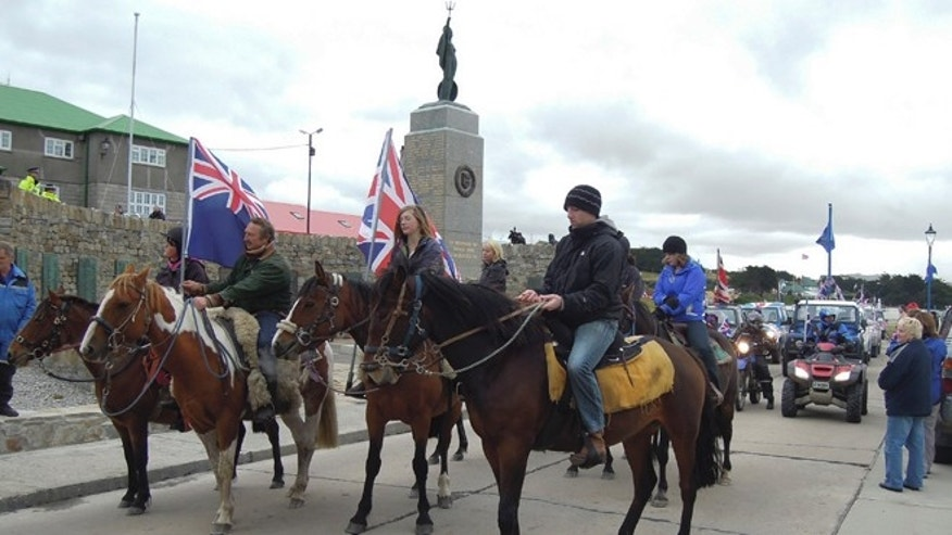 "Residents, some carrying British flags, parade during a rally in support of United Kingdom control over the islands in Port Stanley, Falkland or Malvinas Islands Sunday, March 10, 2013. The local Falkland Islands Government has mobilized a major effort to get registered voters to answer a yes-or-no to the referendum; ""Do you wish the Falkland Islands to retain their current political status as an Overseas Territory of the United Kingdom?"", scheduled for March 10-11, 2013. (AP Photo/Paul Byrne)"