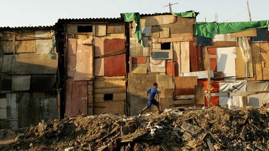A child runs by a row of shacks in Novo Mundo shantytown, Sao Paulo, Brazi, on Thursday, May 18, 2006. Poor youths with little perspective for a better life are the recruiting grounds for organized crime, local community leaders and experts say. (AP Photo/Victor R. Caivano)