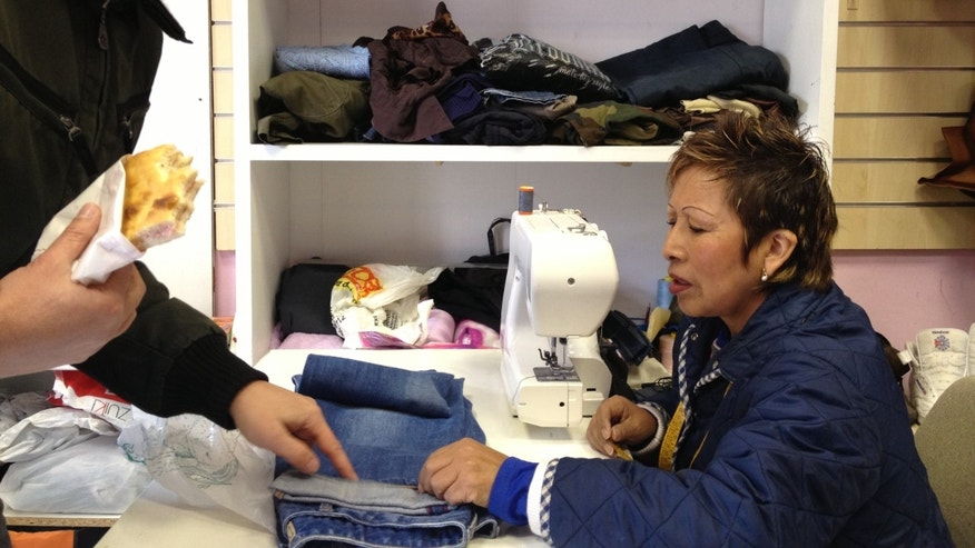 """Bertha Llacsa, 50, with a customer at the Peruvian-owned """"Calzolaio Riparazioni"""" or Calzolaio Reparations"""" in Monte Mario, an immigrant community 15 minutes north of Vatican City."""