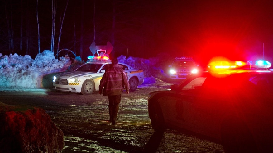 March 17, 2013: Police vehicles block a road just outside the town of Chertsey, Quebec, during a search for escaped prisoners. A dramatic daylight jailbreak involving two Quebec inmates climbing a rope into a hovering helicopter swiftly escalated into a large police operation Sunday night in which at least one escapee was tracked down hours after he fled.