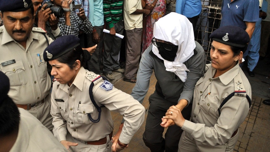 March 16, 2013: A Swiss woman, center, who, according to police, was gang-raped by a group of eight men while touring by bicycle with her husband, is escorted by policewomen for a medical examination at a hospital in Gwalior, in the central Indian state of Madhya Pradesh.